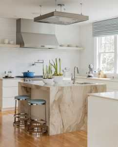 The open plan kitchen allows family and friends to engage while the food prep and cooking are happening. Light colors and clean lines give the space a calming feel.