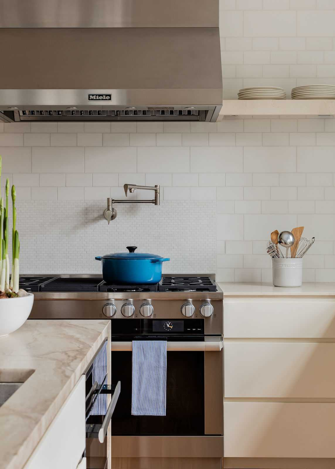 A pot filler above the professional style range and hood is another functional touch for serious cooking.